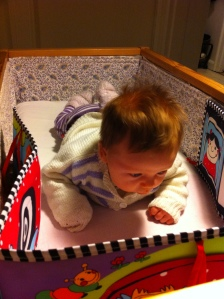 """A two months old """"reading """" her first book on her stomach"""