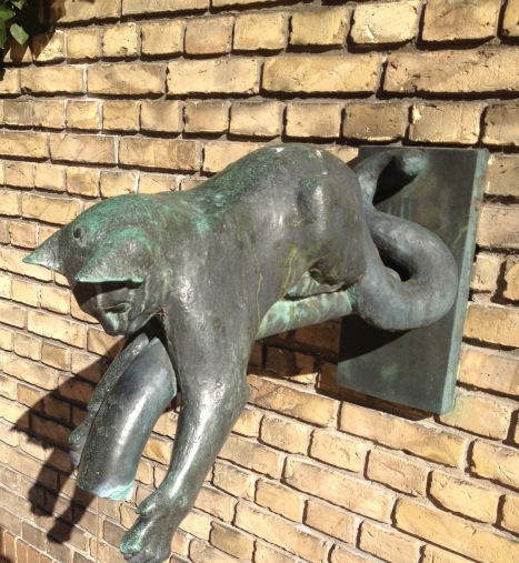 A bronze cat as a decoration on the wall in the patio of the University building