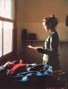 Young woman reading a letter with a baby on the bed Tom Hunter(born 1965)