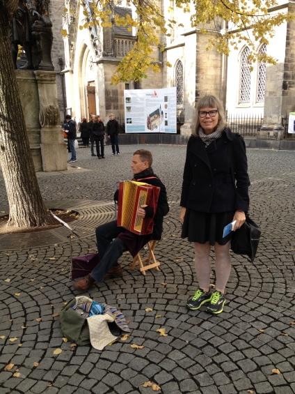A musician playing Bach in front of the Bach Museum and Thomas Church in Leipzig