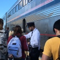 The conductor at Salinas train station helps passengers to get their right places in thetrain
