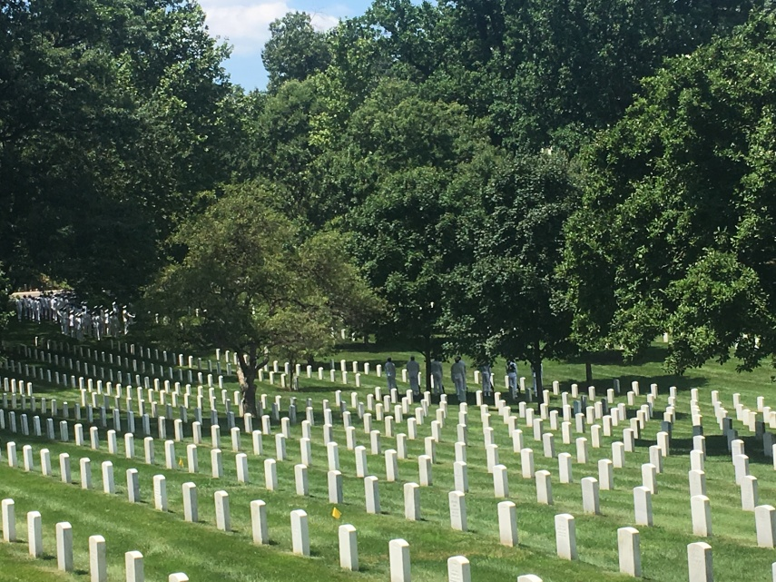 Arlington Cemetery graves and a group of Navy soldiers waiting for a funeral