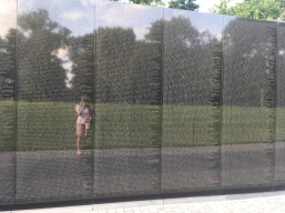 Washington Vietnam memorial with all the names of the fallen reflecting people and nature around