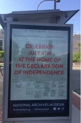 A bus stop poster in the DC capitol area on The Declaration of Independence document shown in The National Archives