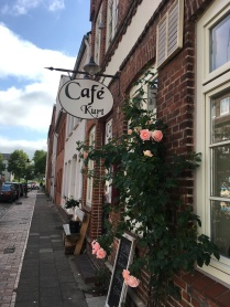 A cafe sign and roses on the wall in Friedrichstadt