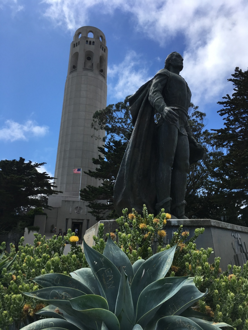 A statue of Christopher Columbus at the feet of the Coit Tower