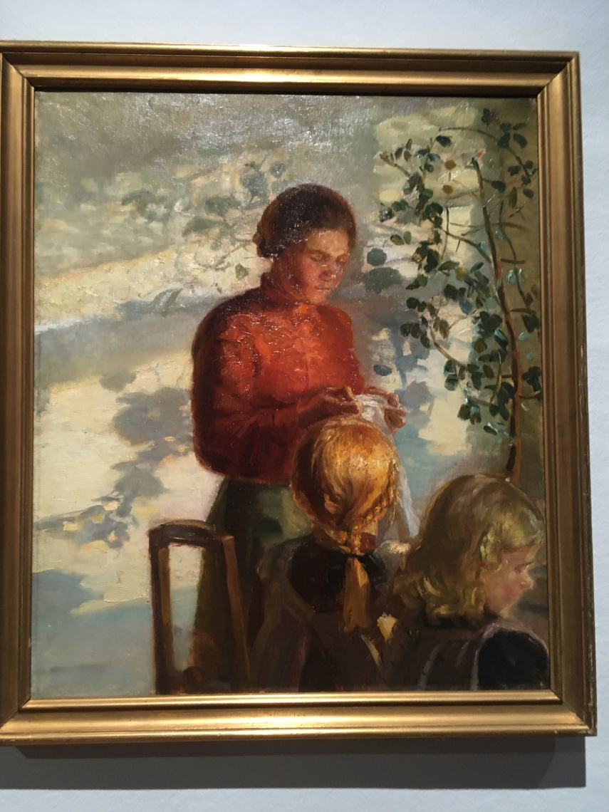 A mother is helping her daughters by Anna Ancher