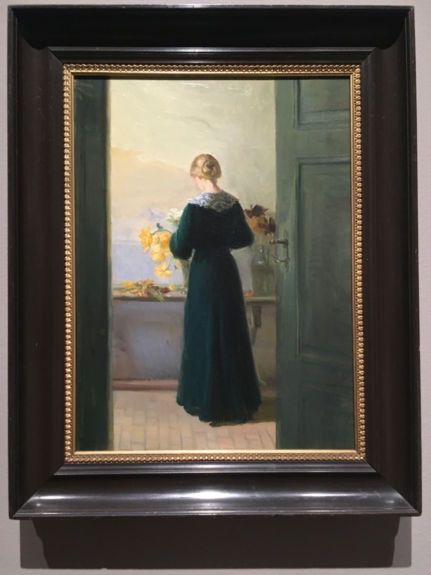 A young woman arranging flowers 1905 by Anna Ancher (1859-1935)