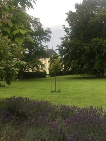 A glimpse of the Gavnø Castle behind lavenders and a lawn and trees